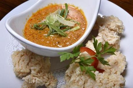 Nataing appetizer of ground pork simmered in coconut milk with garlic and peanuts, served with crispy rice.